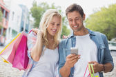 Couple looking at smartphone on shopping trip — Stok fotoğraf