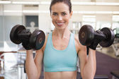 Smiling woman lifting heavy dumbbell — 图库照片
