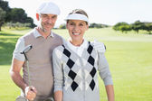 Golfing couple smiling on the putting green — 图库照片