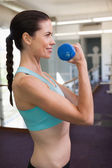 Woman lifting blue dumbbell — Stock fotografie