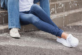 Hip couple in denim sitting on steps — Stock Photo