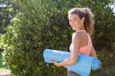 Woman holding exercise mat in the park — Stock Photo
