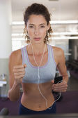 Fit focused woman running on the treadmill — Stock Photo
