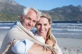 Couple assis sur la plage sous couverture — Photo