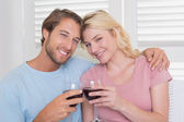 Couple having red wine on the couch — Stock Photo