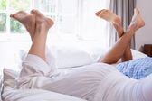 Couples legs lying on bed — Stock Photo