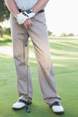 Golfer standing with club — Stock Photo