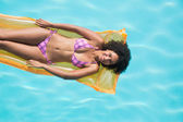 Woman lying on lilo in swimming pool — Stock Photo
