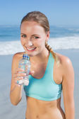 Fit woman on beach taking drink — Stock Photo