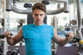 Man using weights machine for arms — Foto Stock