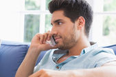 Man making a call on the couch — Stock Photo
