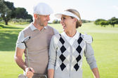 Golfing couple smiling on the putting green — Stockfoto
