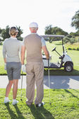 Golfing couple looking out to the course — Stock Photo