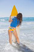 Mädchen am strand mit surfbrett — Stockfoto