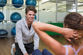 Trainer helping his client doing sit ups — Stock Photo