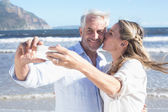 Couple at the beach taking a selfie — Stock Photo