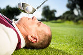 Golfer holding tee in his teeth — Stock fotografie