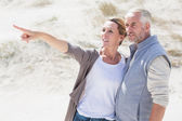 Couple on the beach looking at something — Stock Photo