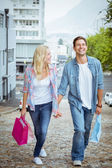Couple on shopping trip walking uphill — ストック写真