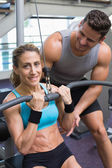 Female bodybuilder using weight machine — Stock Photo