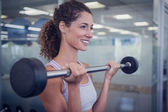 Fit smiling woman lifting barbell — Stock Photo