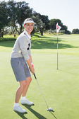 Lady golfer on the putting green — Stok fotoğraf
