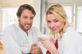 Couple in bathrobes having coffee — Stock Photo