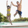 Couple jumping into swimming pool — Stock Photo
