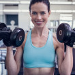 Smiling woman lifting heavy dumbbell — Stock Photo #48341281