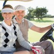 Golfing couple driving in their buggy — Stock Photo #48341813