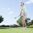 Female concentrating golfer teeing off — Stock Photo #48342121