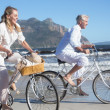 Couple riding their bikes on the beach — Stock Photo #48342417