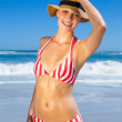 Woman in bikini and sunhat posing on beach — Stock Photo #48342609