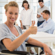 Businesswoman in wheelchair with team behind her — Stock Photo