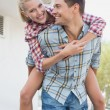 Man giving his girlfriend a piggy back — Stock Photo #48343965