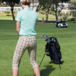 Female concentrating golfer teeing off — Stock Photo