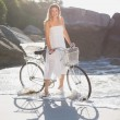 Blonde standing with bike on beach — Stock Photo #48344149