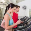 Fit couple running together on treadmills — Stock Photo
