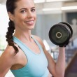 Smiling woman lifting heavy dumbbell — Stock Photo #48345385