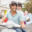 Couple riding scooter with shopping bags — Stock Photo #48345911
