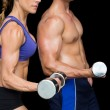 Bodybuilding couple with large dumbells — Стоковое фото