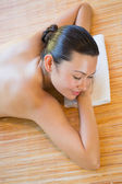 Smiling brunette relaxing on massage table — Photo