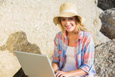 Blonde using laptop at beach — Stockfoto