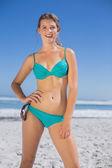 Fit woman in bikini on beach smiling — Stock Photo