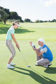 Man coaching his partner on the putting green — Stok fotoğraf