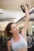 Fit woman lifting up kettlebell — Stock Photo