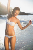 Blonde in bikini at beach with wet hair — Stock Photo