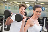 Fit couple lifting barbells together — Stock Photo