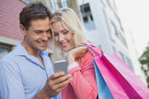 Couple looking at smartphone — Stockfoto