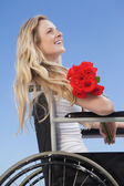 Wheelchair bound blonde holding roses — Stock Photo